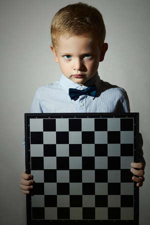 intelligent: Little boy with chessboard.fashion children.Bow-tie.Little genius Child. Intelligent game.Emotion