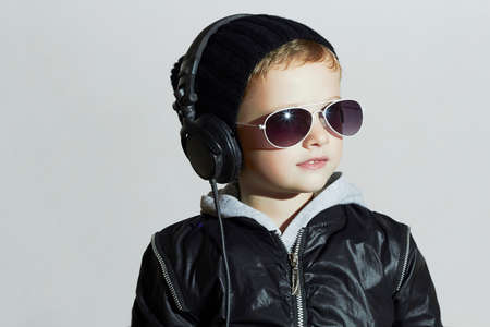 dj boy: little deejay. funny smiling boy in sunglasses and headphones.5 years old child listening music in headphones. DJ kids
