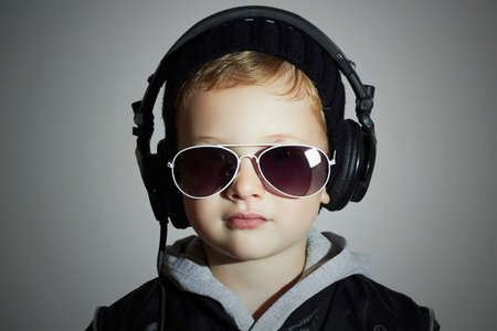 deejay: little deejay. funny smiling boy in sunglasses and headphones.5 years old child listening music in headphones. DJ kids