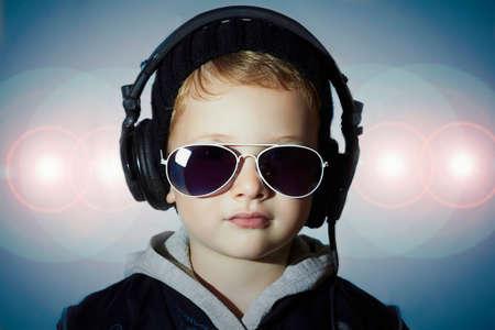 dj boy: little deejay. funny little boy in sunglasses and headphones.smiling child listening music in headphones. DJ. disco lights background