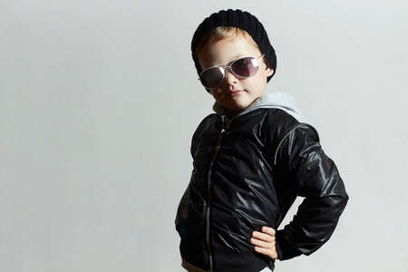 black fashion model: Fashionable child in sunglasses. Kid in Black cap.winter style.Posing Little boy.Children fashion