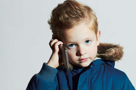 funny little boy talking on the cellphone. modern child in winter coat. fashion kids.children Stock Photo - 46347477