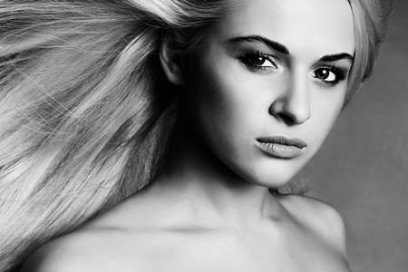 Beautiful Face of Young Woman.Blond girl.close-up.Art monochrome portrait.Beautiful healthy hair.Beauty salon.flying hair