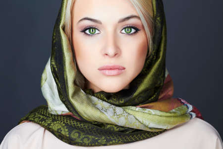 Beautiful blond woman in scarf.winter fashion.Beauty Girl.Classic Russian style.close-up make-up portrait.green cat eyes
