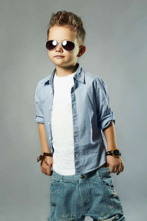 fashionable little boy in sunglasses.stylish kid in jeans. fashion children Imagens