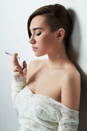 short haircut: beautiful young woman with short haircut smoking cigarette.Hairstyle.sweet girl in a wedding dress