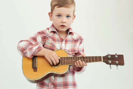 funny child boy with guitar.ukulele guitar.country boy playing music 免版税图像 - 50408830