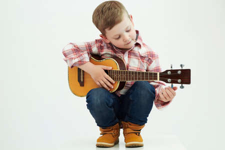 cute young boy: funny child boy with guitar.ukulele guitar.country boy playing music