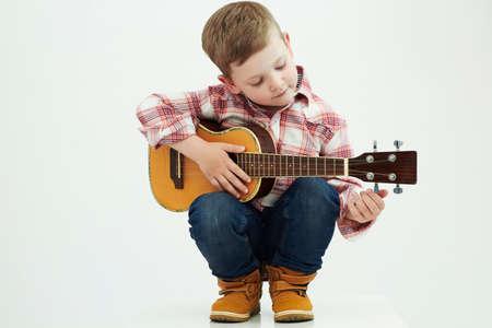 grappig kind jongen met guitar.ukulele guitar.country jongen het afspelen van muziek