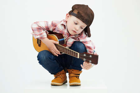 funny child boy with guitar.ukulele guitar. fashionable country boy playing music Foto de archivo
