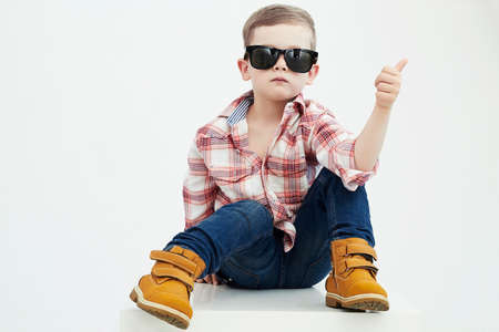 Funny child.fashionable mały chłopiec w sunglasses.stylish dziecko w żółtych butach