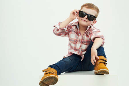 teen boy face: Funny child.fashionable little boy in sunglasses.stylish kid in yellow shoes