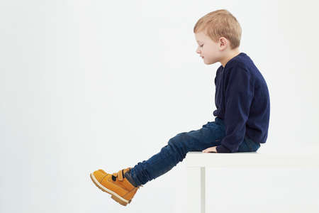 Fashionable child in yellow boots. fashion kids.children.little boy sitting on a table Stock fotó