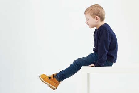 kinderen: Modieuze kind in gele laarzen. mode kids.children.little jongen zittend op een tafel