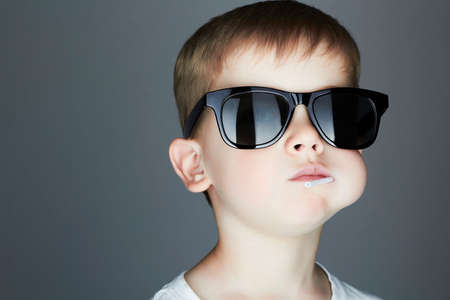 cute young boy: Funny Young Boy Eating A Lollipop.Fashionable child in sunglasses