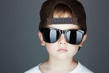 rapero: Estilo poco boy.Hip-Hop. children.handsome moda en sunglasses.in Sombrero Tracker. El rapero Young. Ni�o grave en Cap Foto de archivo