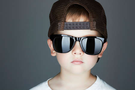 rapper: little boy.Hip-Hop Style. fashion children.handsome in sunglasses.in Tracker Hat. Young Rapper. Serious Child in Cap