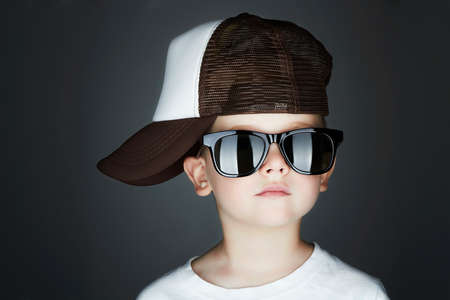 cute young boy: little boy.Hip-Hop Style. fashion children.handsome in sunglasses.in Tracker Hat. Young Rapper. Serious Child in Cap