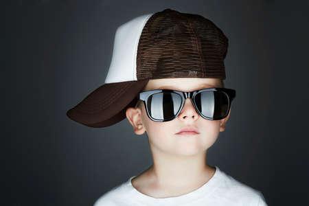 Trochę Styl boy.Hip-Hop. Moda children.handsome w okulary słoneczne.W Tracker Hat. Młody raper. Poważne Dziecko w Cap Zdjęcie Seryjne