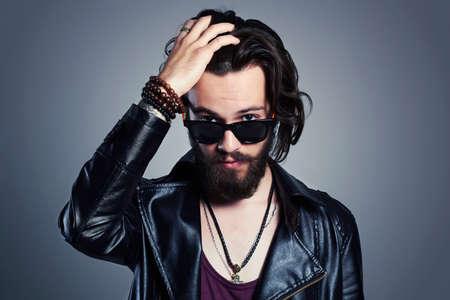 volto uomo: giovane uomo barbuto in una giacca di pelle. Hipster in occhiali da sole Archivio Fotografico