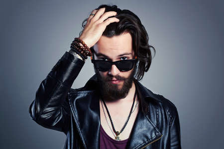young bearded man in a leather jacket. Hipster in sunglasses Stock Photo