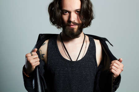fashionable young bearded man in a leather jacket. Hipster