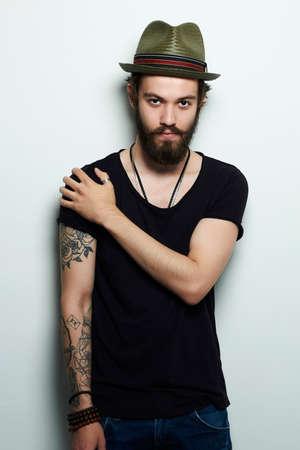 帽子でハンサムな男は。タトゥーを持つ残忍なひげを生やした少年