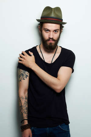 cute tattoo: handsome man in hat.Brutal bearded boy with tattoo