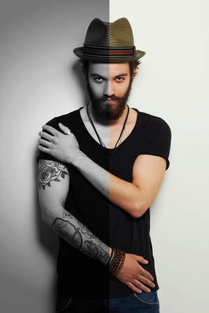 handsome man in hat.Brutal bearded boy with tattoo