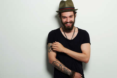 young man. Smiling Hipster boy.handsome man in hat.Brutal bearded boy with tattoo Standard-Bild