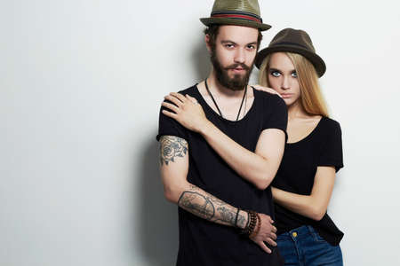 fashion beautiful couple in hat. Hipster boy and girl. Bearded young man and blonde. Tattoo
