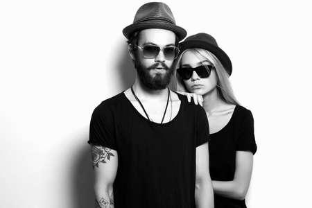 mooie gelukkige paar in de hoed. Hipster jongen en meisje. Bebaarde jonge man en blonde model in zonnebril Stockfoto