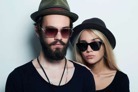 adult boys: fashion beautiful couple in hat together. Hipster boy and girl. Bearded young man and blonde in sunglasses Stock Photo