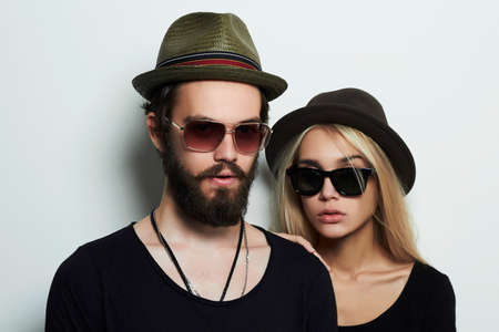 fashion sunglasses: fashion beautiful couple in hat together. Hipster boy and girl. Bearded young man and blonde in sunglasses Stock Photo