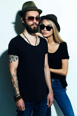 two boys: beautiful happy couple in hat. Hipster boy and girl. Bearded young man and blonde model in sunglasses