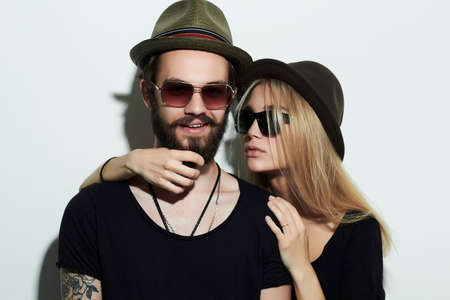 blonde boy: fashion beautiful couple in hat wearing trendy glasses together. Hipster boy and girl. Bearded young man and blonde in sunglasses