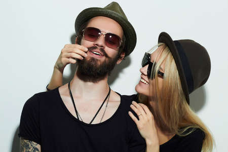 blonde boy: fashion beautiful happy couple in hat wearing trendy glasses together. Hipster boy and girl. Bearded young man and blonde in sunglasses