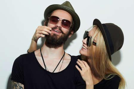 fashion mooie gelukkige paar in de hoed draagt trendy bril samen. Hipster jongen en meisje. Bebaarde jonge man en blonde in zonnebril Stockfoto