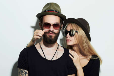 fashion beautiful couple in hat together. Hipster boy and girl. Bearded young man and blonde in sunglasses Stok Fotoğraf