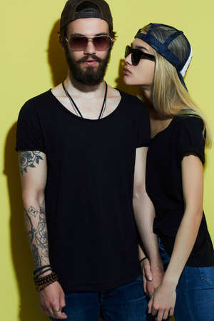 fashion beautiful couple together. Tattoo Hipster boy and girl. Bearded young man and blonde in sunglasses Imagens