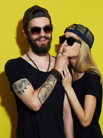 fashion beautiful couple together. Tattoo Hipster boy and girl. Bearded young man and blonde in sunglasses Stock fotó