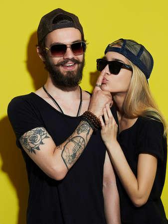 Hermosa pareja de moda juntos. Tatuaje del inconformista chico y chica. hombre joven con barba y rubio con gafas de sol Foto de archivo - 52081484