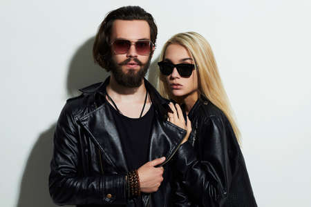 fashion beautiful couple in black clothes wearing trendy glasses. Hipster boy and girl. Bearded young man and blonde in sunglasses Archivio Fotografico