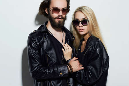 fashion beautiful couple in black clothes wearing trendy glasses. Hipster boy and girl. Bearded young man and blonde in sunglasses Stock Photo