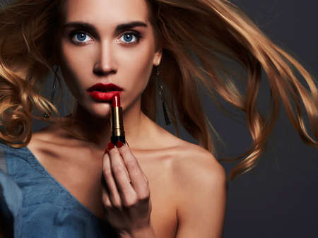 fashion portrait.beautiful girl with red lips. young Woman putting red lipstick. flying blond hair