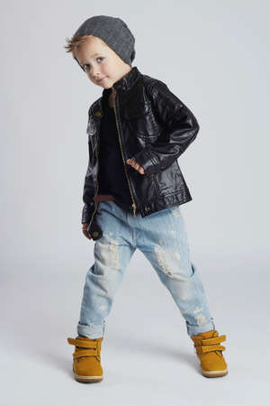 Funny child.fashionable little boy in hat.stylish kid in yellow shoes.winter fashion children 免版税图像 - 60224936
