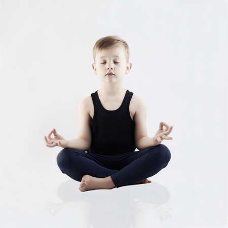 Relaxed child does yoga.handsome little Boy Stock Photo
