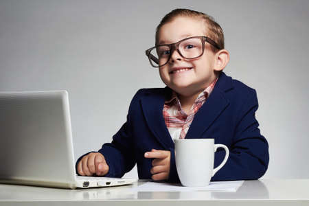 Young business boy. smiling child in glasses. little boss in office.funny kids