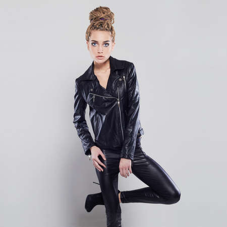 sexy beautiful girl in leather with dreadlocks hairstyle. punk rock blond young woman in latex and high heels