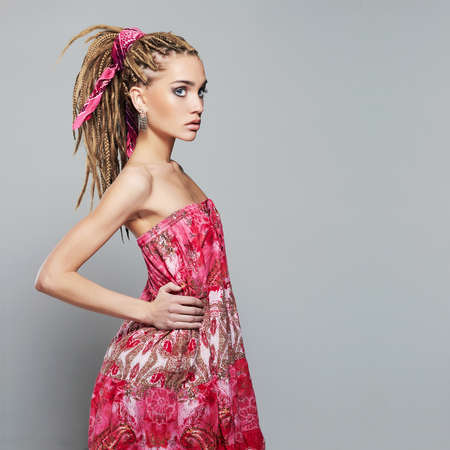 beautiful girl with dreadlocks. pretty young woman with African braids hairstyle. pink dress 免版税图像